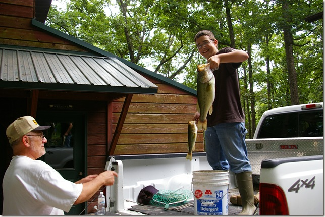 Travis holding up a small and large fish with Jim looking on