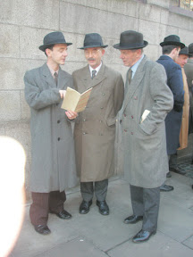 Darragh dressed in hat, long coat and scarf, posing with other guys in similar 1930s attire