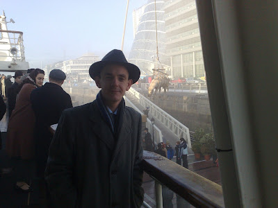 shot of Darragh in hat, scarf and coat with cow and National Conference Centre in the background