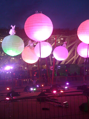 photo shows a number of giant, inflatable spheres in different luminous colours with people on them