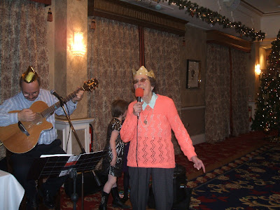 An old woman obviously enjoying singing along with a band in a big Hotel room. A Christmas tree is visible in the corner.