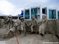 Statues of children enjoying music. Behind them is the New City Hall in Tagum City.