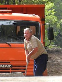 Водитель камаза со щебнем, работающий на строительстве дороги, передвигает бетонные блоки, которые должны были препятствовать проезду тяжёлой техники через рельсы МЮЖД.