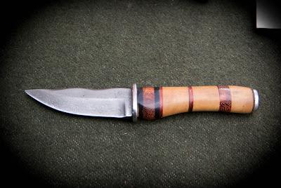 Couteau de chasse, lame en acier damas forgée à partir d'un câble de grue. Garde en acier inoxydable, manche multi-bois (ébène, buis, palissandre et cuir).