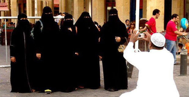 An Arabian person is taking photographs of women in veils