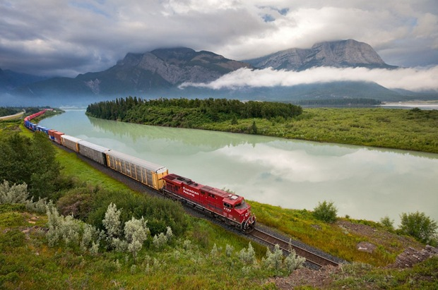 Canadian Pacific Railway train passes an amazing green landscape at Exshaw, Alberta, Canada