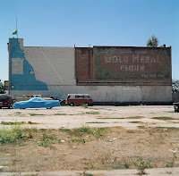 Date: Spring 2006<br /> Location: Guadaloupe, California, Route 1</p> <p>The drive from San Francisco to San Diego product a bevy of nice pictures.</p> <p>We came across this town that looked like it came out of a cowboy film. We turned a corner and here was this town, one street, a bunch of buildings, some parked cars. We were waiting for the horses to make their entrance. We drove by this wall, and were half way down the road when I decided to go back and take the picture. It was just too tempting.</p> <p>The juxtaposition of the colours on the wall with the colours of the cars. Too hard to resist.