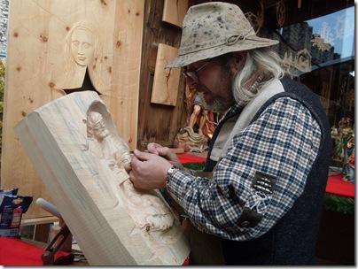 un artista lavora alla sua opera al mercatino di trento