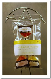 one plastic bag of fruit-flavored lollipops hanging from a chome stand