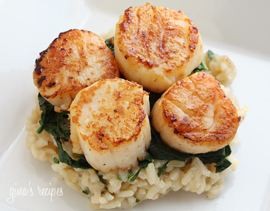 These seared sea scallops over wilted spinach and parmesan risotto is an elegant dish, perfect for a special occasion.