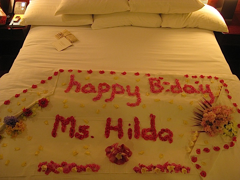 a floral birthday greeting on our bed at Bellarocca Island Resort
