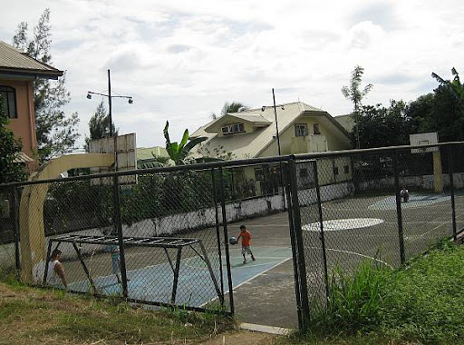 concrete basketball court in a middle-class neighborhood