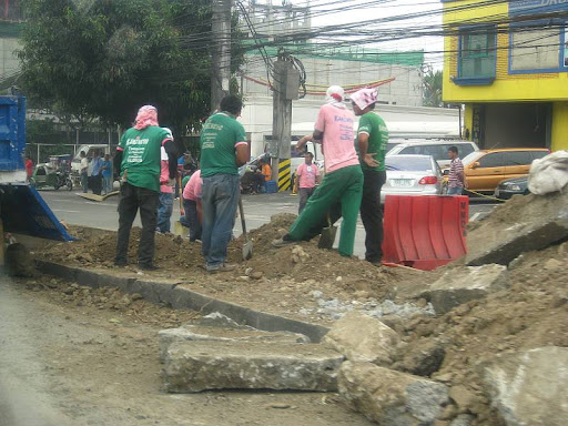 Metropolitan Manila Development Authority (MMDA) workmen clearing road rubble after uprooting acacia trees along Katipunan Avenue