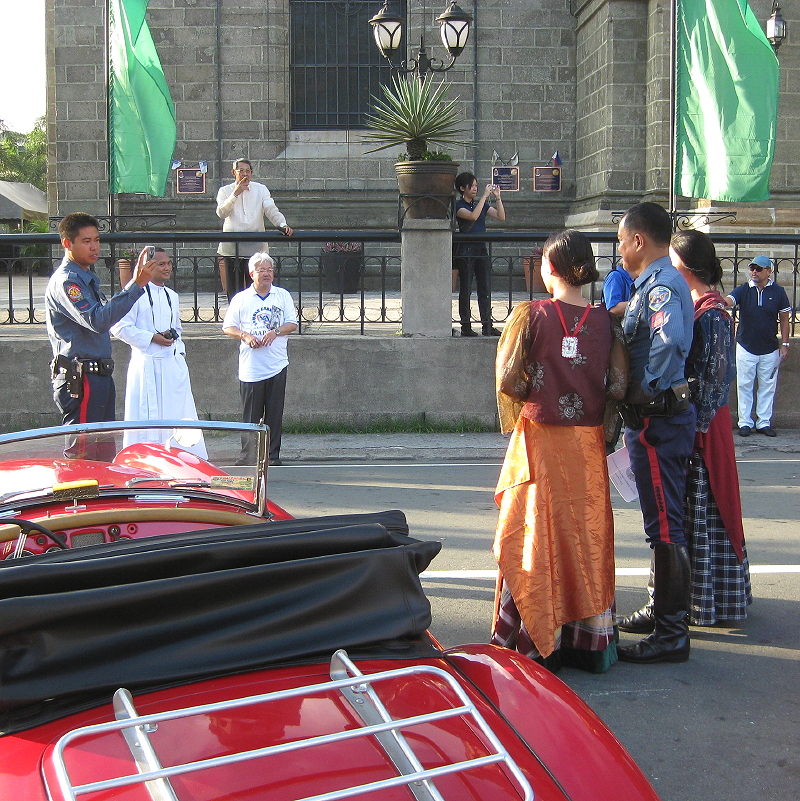 cop posing with costumed student-actors in Intramuros