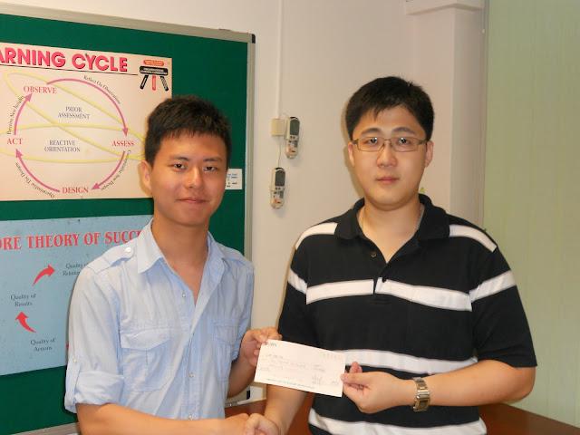 Chua Chee Tek (left) receiving the Bursary Award from AJCAA President Lau Kiat Meng.