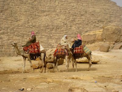 Three men riding camels at the pyramids in Cairo