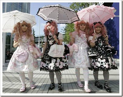 Quatro garotas andando em ruas movimentadas no Japão, vestidas de Lolita com sombrinha e tudo. Leia o post para entender o que é isso.