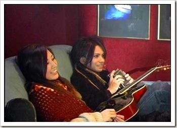 O casal no mesmo sofa assistindo tv.