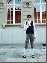 Um rapaz vestido com ouji em frente a uma construção antiga. Que yume!