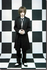 Um lindo dandy gothic na frente de uma sala toda xadrez. Que luxo!