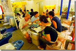 I clienti siedono su water con tanto di tavoletta colorata e sciacquone e mangiano sui lavandini