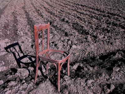 abstract. un camp arat. un scaun. o zi cu soare