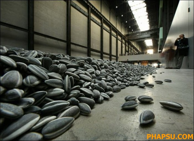 Chinese artist Ai Weiwei poses with some seeds from his art installation 'Sunflower Seeds' in London, Monday, Oct. 11, 2010. The specially commissioned art piece takes the form of a field of sunflower seeds inside the Turbine Hall at Tate Modern gallery,  made of over 100 million handmade unique porcelain replicas of sunflower seeds, made by Chinese Artist Ai Weiwei, and will run until May 2, 2011. (AP Photo/Lennart Preiss)