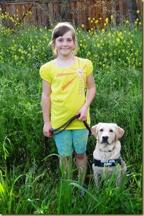 My niece Sara standing in a field of yellow mustard flowers with Reyna sitting next to her in her puppy coat.  Sara has a very cute smile on her face.