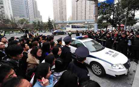 Police officers keep a throng of reporters and extraordinary onlookers at the back of military fasten as a car enters the Shanghai No.1 Intermediate People