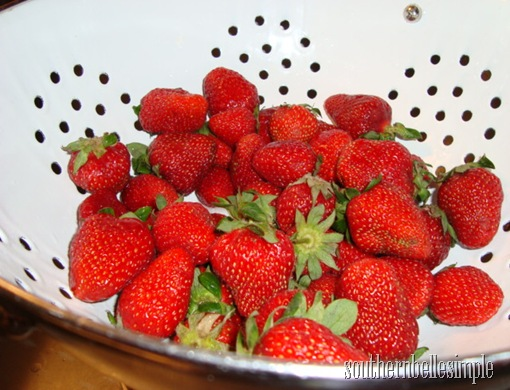 strawberries in white colander
