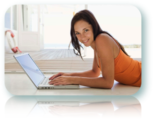 A smiling woman using a laptop to apply for a payday advance loan.