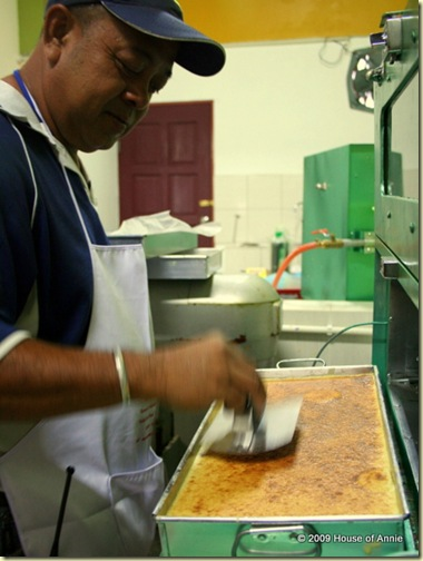 pressing down last layer of sarawak layer cake - copyright house of annie