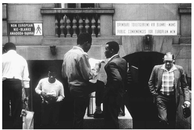 "A Segregated Lavatory in South Africa. A group of men stand in front of a lavatory in apartheid-era South Africa with separate entrances for ""European "" and ""non-European'' men."