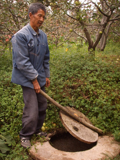 The next climate defender standing over his biogas digester in rural Yunnan.