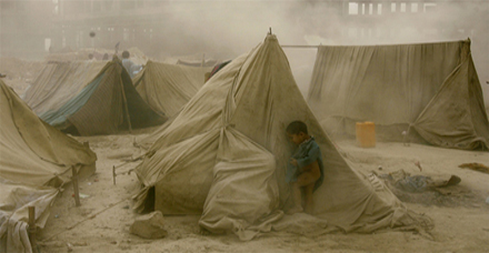 An Afghan refugee child hides from a dust storm