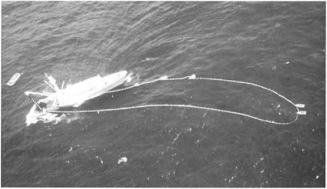 Backdown procedure in progress. As the tuna vessel moves backward, the net is drawn into a long channel. The corkline at the far end is pulled underwater slightly, and the dolphins escape. Speedboats are positioned along the corkline to help keep the net open.