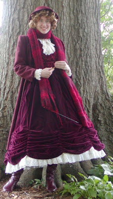 Young woman wearing mid-calf length Victorian gown in burgundy, somewhat ruched up at the bottom to expose a lacy petticoat. She wears burgundy lace-up boots, a white lace jabot, and is knitting an enormous burgundy scarf that is looped around her neck. She is smiling at the viewer, has curly brown hair, and is wearing a dainty burgundy hat.