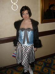 A young woman wearing a flapper-style dress with an applique'd bow tie and an off-the-shoulder fuzzy coat, much like the Second Doctor.