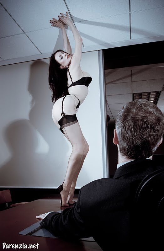 a woman wearing stockings, panties and a bra stands on conference room table in an office and touches the ceiling
