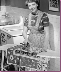 woman ironing in kitchen