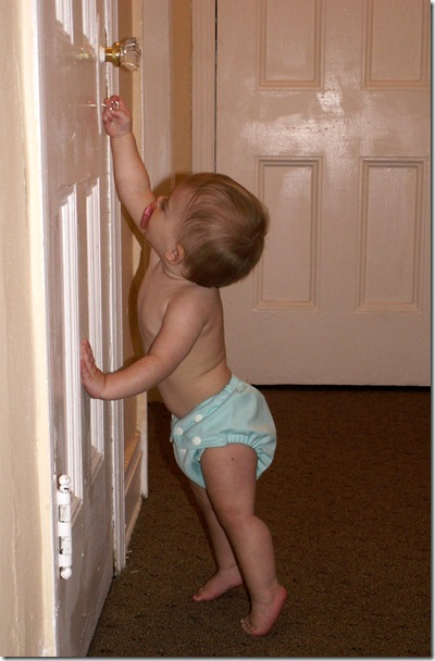 Elaine 10 months reaching for doorknob