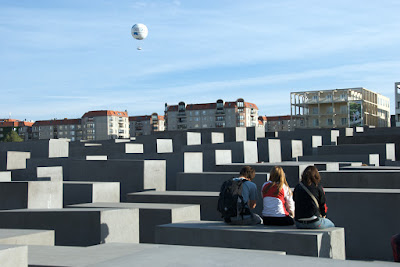 people sitting on stone columns Memorial to the Murdered Jews of Europe berlin