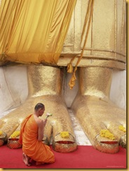 252-10492~Buddhist-Monk-Kneeling-in-Prayer-at-the-Feet-of-a-Statue-of-the-Standing-Buddha-Thailand-Posters
