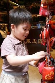 挑皮包,在台灣常見的東西對祐祐來說倒也稀奇,讓他看足了十二生肖造型包再走也不遲。