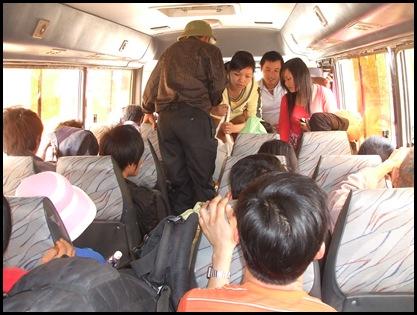 El minibús lleno y gente pasando por encima las bolsas en el suelo