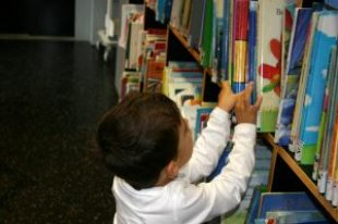 A small child reaching for books on a shelf