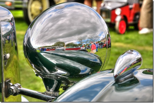 reflections in headlamp and bodywork of classic mg sportscar