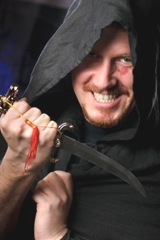 medieval looking menacng man with dagger wearing black cloak with hood