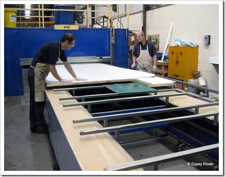 Next large sheets of 40mm polystyrene are placed on the glue. It then goes through the spray booth for another dose of glue before the plastic sheet goes on top. It is then heated and compressed for 15 minutes.