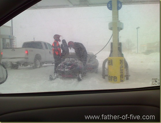 Snowmobiles gassin' up at the pumps, right next to cars and trucks!
